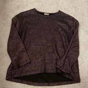 En mörk lila och svart tröja, emo vibes. Det står 7 år men  den är rätt så lång till en 7 årig satt den funkar bra om en 10-14 årig skulle ha den som magtröja