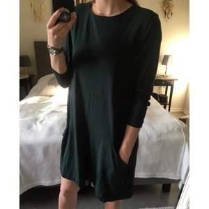 Mörkgrön löst hängande klänning. Medeltjockt tyg. Fickor på nedre framsidan. Trekvartslånga ärmar 👗