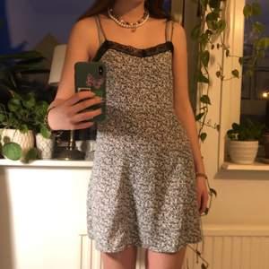 söt miniklänning med grått/blått blommigt mönster och spetsdetaljer köpt second hand! klänningen har justerbara band och passar en XS-S. tyvärr har klänningen spruckit på vänstra sidan, men det syns inte speciellt mycket när klänningen är väl på :)