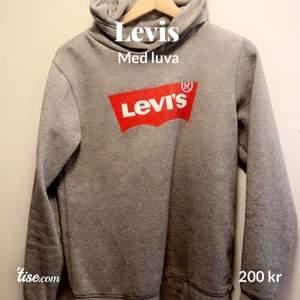 En snygg grå Levi's  Med luva  Med sitt röda Levis märke  som small  sitter verkligen efter kroppen