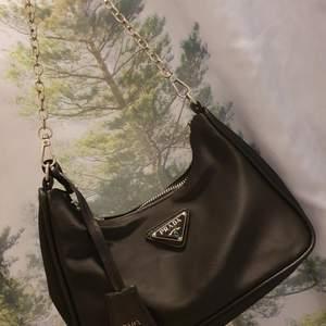 Remake replika Prada handväska i svart nylon. Handtag går att ta loss och byta ut om man önskar det. Klassiska loggan på väskan och dragkedja. Ej blivit använd så väskan är i nyskick! Tveka inte att skriva vid funderingar <3