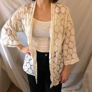En vit kimono kaftan med vita blommor i tyget. Frakt tillkommer på 50 kronor.