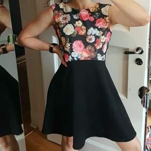 Superskön klänning, med blommig överdel, figursmickrande sömmar och svart böljande kjol. Dragkedja i ryggen (syns på 3e bilden).