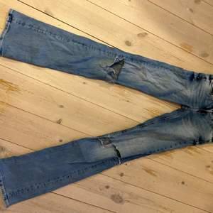 Lågmidjade bootcutjeans med hål på knäna från Tommy Jeans i strl 24/30. Jeansen har en reva (se bild). Annars är de i bra skick. Säljer pga de är för små. Innerbenslängd: 85 cm. Fler bilder kan skickas!💙