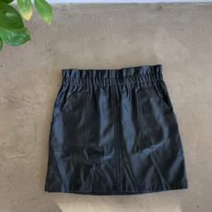Svart kjol i läderimitation! Skulle säga att den är storlek 38 men passar även 36:or då den har resår baktill:) Kjolen har även två fickor fram vilket är GULD värt!