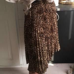 Plisserad kjol i leopard mönster, nytt skick. Storlek S men passar mindre och större då den har ett resårband vid midjan som är töjbart.