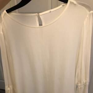 En vit blus med utsvängda armar. Storlek S