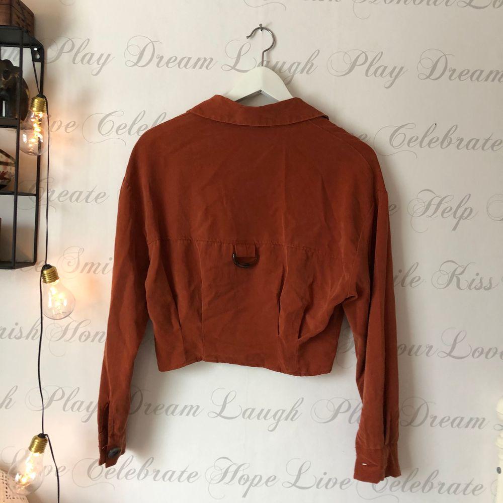 Blus i 80-tals-stil. I en mörkröd/ brun färg. Bruna stora knappar :). Blusar.
