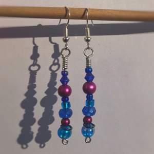Fina långhängande örhängen gjorda med lila och blåa pärlor. Kan fraktas och hämtas upp i Stockholm/Huddinge. Skriv vid frågor!