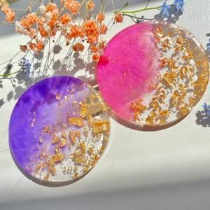 Handgjort glasunderlägg  som gjord av epoxy resin.   Vad är Epoxy resin? Epoxy Resin är en självtorkande massa som skapar en transparent och glänsande yta som påminner om glas när den har torkat.  I detta produkt blandar jag epoxy resin med pigment färg och guld flakes.