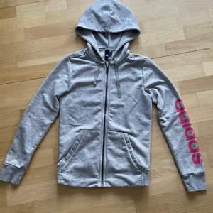 Jättefin Adidas zip up hoodie eller huvtröja i ljusgrå färg med rosa tryck☺️ Använd fåtal gånger så är i mycket bra skick och i storlek S dam. Den är ganska tunn med sköna fickor och perfekt att träna i eller ha till vardags:) Kontakta gärna vid frågor, fler bilder eller om du vill köpa💕 Frakt tillkommer på 62kr!
