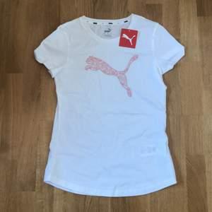 Vit puma träningst-shirt med ljusrosa tryck på framsidan. Aldrig använd - taggen kvar