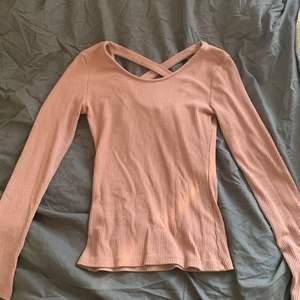 En rosa tröja med kors i ryggen har klippt av lappen så vet inte märke eller så men tror den kommer ifrån Ginatrico och är en s i storlek