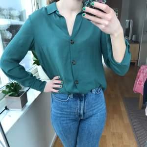 En otroligt fin grön blus i storlek 36 från Gina Tricot. Passar bra både som vardagsplagg och vid festligare tillfällen! Den gröna färgen ser mörk ut på bilderna men är finare i verkligheten! De bruna knapparna gör den unik. Blusen är endast använd ett fåtal gånger så den är i ett mycket bra skick!