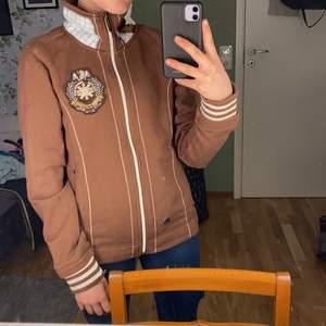 En brun HV POLO tröja med detaljer. Använd men i bra skick.