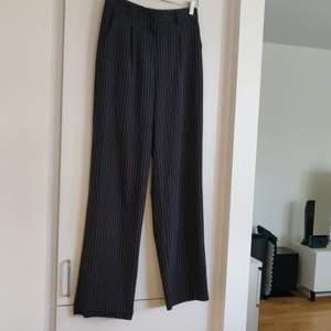 Mörkblå kritstrecksrandiga byxor från Na-kd i storlek 36. Passformen är tajt över midja/rumpa sedan rakt fall med vida ben. Fraktkostnaden tillkommer.