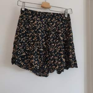 Svart kjol med blommor i tenniskjol modell från Bikbok i storlek S. Fraktkostnaden tillkommer.