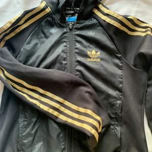 Adidas tröja med guldiga sträck och luva. De är ett glansigare material fram till med adidas loggan. Använd skick. Storlek 36