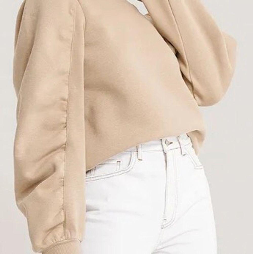 Sweatshirt från NA-KD, beige med lite ballongärm, rå kant nertill och vid i modellen, supersnygg! Knappt använd. Strl xs. . Tröjor & Koftor.