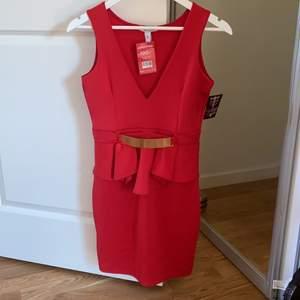Röd klänning med gulddetaljer från Nelly, aldrig använd! Prislappen är kvar.  ✨ Köpt för 100 kr, säljer för 80 kr! Vid stort intresse startas budgivning ❤️