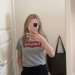 Grå t-shirt med röd logga från Levi's. Köpt på barnavdelningen men passar en XS/ XXS. Endast testad, aldrig använd☺️