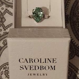 Mini Drop Ring Rhodium Peridot Delite 495 kr  Mini Drop Ring Rhodium Peridot Delite från Caroline Svedbom. En öppen ring med en vacker droppformad Swarovskisten i en kungligt, ljus grön färg.   Mått: 13 x 10 mmStorlek: One size, justerbar Material: Rhodiumpläterad mässing & Swarovisk-kristall