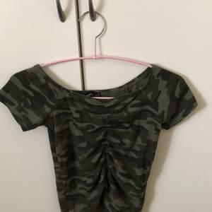 En jättefin off shoulder tröja i militär mönster. Stolek S. Använd ett fåtal gånger, fint skick.