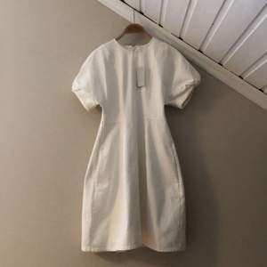 Vit jeansklänning med fickor från COS. Aldrig använd, nypris 790kr. Klänningen är figursydd och har puffärmar och dragkedja i ryggen. Klänningen är i strl. 34 men passar lika bra på någon med strl. 36.
