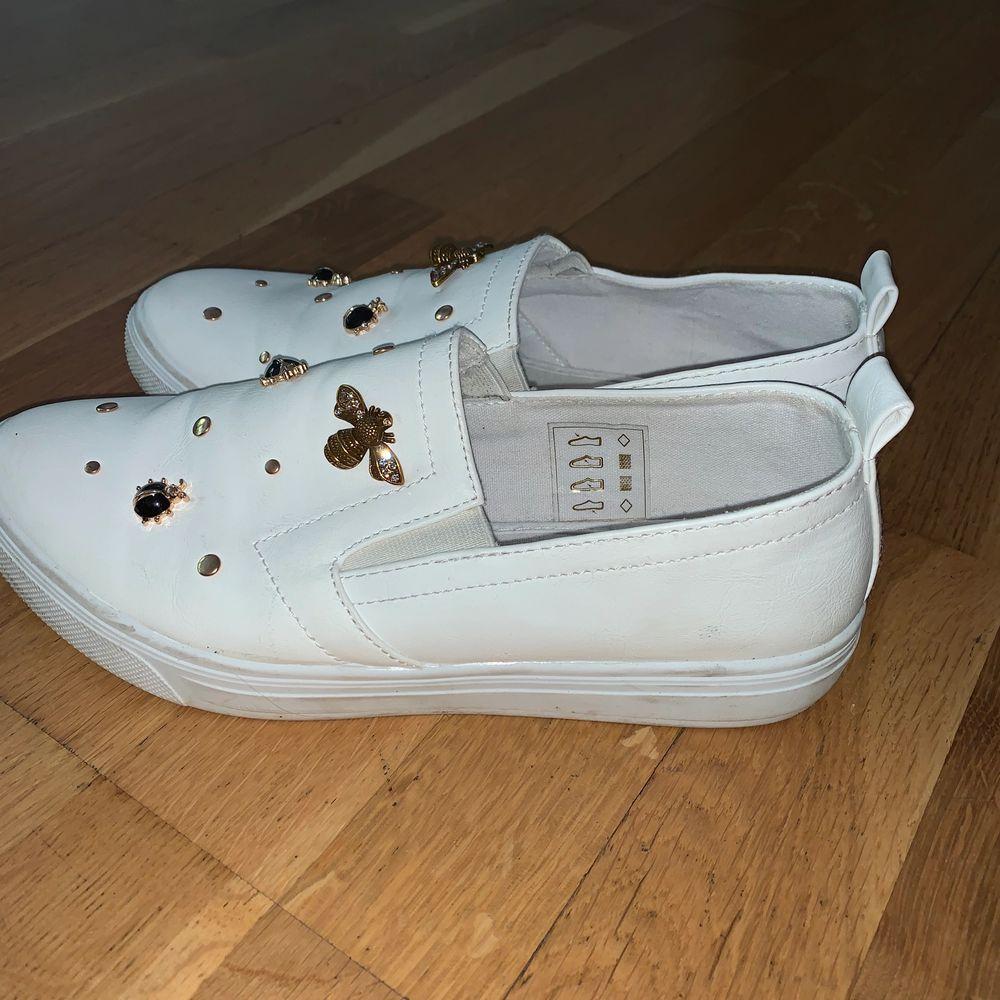 Vita slip on skor med fina våriga dekorationer 😋. Skor.