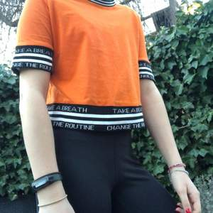 Orange tröja med textdetaljer i kanterna. Tröjan har andvänds 2-3 gånger. Den är köpt på en butik i Frankrike som heter Jennyfer.