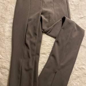 Snygga brun/gråa byxor med slits där fram, ur snygga men kommer inte till användning! Sömmen har släppt lite där fram men annats är dom i superfint skick, när man har på dig dem syns de knappt och det går att sy ihop lätt!😊