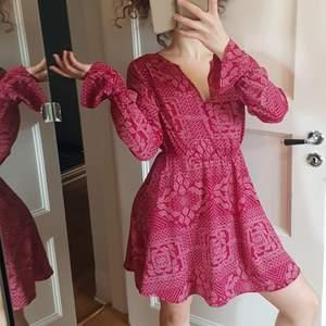 Röd mönstradklänning från Ivyrevel, v-ringad, i ett lätt, skönt, luftigt material. Något tajt i resåren i ärmarna, rekommenderar storlek XS-S.