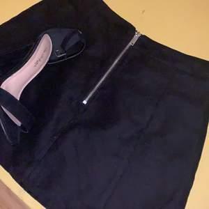 En svart kjol med dragkedja fram. En tajt passform och kort längd. Använd ett fåtal gånger och är i bra skick🍸