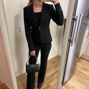 Svart figursydd kavaj från H&M i storlek 34, helt ny har bara hängt i garderoben sedan den köptes. Nypris är 350kr!