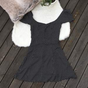 Svart/vit prickig klänning med urringning i ryggen. Står storlek L men passar mig som har M. Dragkedja baktill. Använd en gång. Frakt ingår i priset.