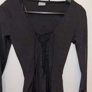 En snygg svart tröja med snörning från Ginatricot. Aldrig använd då den tyvärr är för liten. Storlek XS. Frakt tillkommer