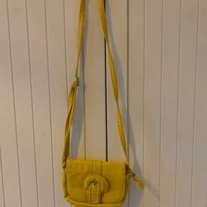 En gul handväska med olika fack. Lite sliten på vissa ställen men syns inte super mycket💕
