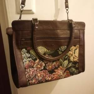 En stor vintage handväska med blommigt tyg. Vet ej om de är äkta skin. Den är rymlig med 3 fack.