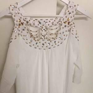 Vit klänning med silvriga och guldiga paljetter på bröstet  Storlek M  Aldrig använd  I väldigt bra skick