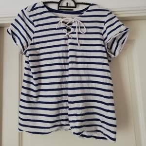 Fin tshirt med knytning. Har 2 mindre fläckar framtill men annars felfri. Skicket är bra.