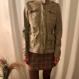 Milititary style jacket in beige fake leather, great fit with possibility for a belt around the waste. Silver buttons and zipper.