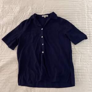 Marinblå skjorta med korta ärmar i strl L. Bröstfickor med broderingar och silvriga knappar finns.