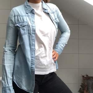 En jeansskjorta från märket ONLY. Ett liiitet hål under vänstra armhålan men inget som syns. Kan knäppas upp på mindre storlekar men passar bra som på bilden för storleken M.