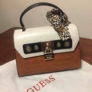 Äkta Guess handväska ☺️köpte föra året, men använd sparsamt . Ny pris 1499 mitt pris nu 700😊 Fin handväska och i lagom bra storlek  . Dust bag med följer 😛 frakt 104 kr . Pris kan diskutera vid snabb affär .