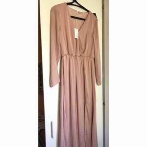 Supergullig långklänning från NLY Trend. Köpt förra sommaren men har blivit hängandes i min garderob, alla lappar kvar. En fin ljusrosa dov färg och skönt material  Köparen står för eventuell frakt.