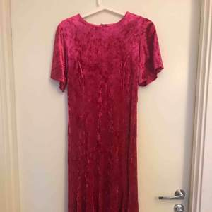Klänningen är figursydd och vintage-inspirerad. Väldigt fin vid ärmarna och även nertill klänningen. Färgen är rosa.  Midiklänning. Den är aldrig använd och ca 4 veckor gammal, så helt ny.