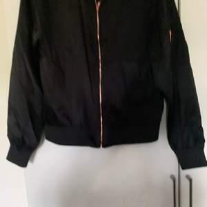En oanvänd svart bomberjacka med rosé färgad dragkedja säljes för 150kr inklusive frakt. Storlek M
