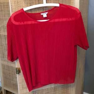 Röd plisserad topp från monki, endast använd en gång. Lätt transparant.