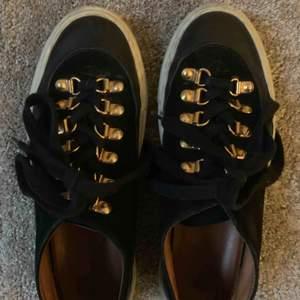 Sneakers i svart mocka med gulddetaljer från svenska Rodebjer. Mycket fint skick!