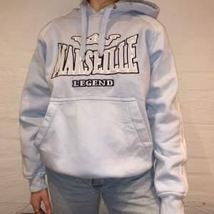Dags för första släppet!                                             Vi säljer denna baby blue hoodie ifrån Marseille Legend. Priset är 299kr. Den är i storlek L och passar som en M. Personen på bilden är 165 och brukar ha på sig M. Det finns en del fläckar som inte riktigt syns om inte man kollar noga. Vi skickar bild vid intresse av köp. Kontakta oss på Plick eller vår Instagram @wanderetro. Om flera visar intresse blir det budgivning. Köparen står för spårbar frakt på 66kr. 🤍
